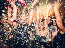 Confetti falling over a smiling group of people on a dance floor of a nightclub