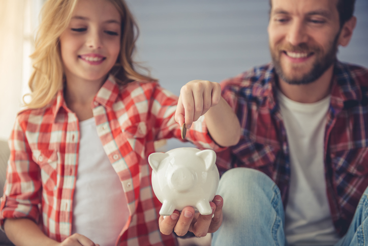 Pretty girl is putting a coin into a piggy bank that her handsome father is holding. Both are smiling while sitting on sofa at home