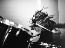 A 9 year old girl has fun playing a drum set in her room, working on songs for her band.  High contrast black and white image.